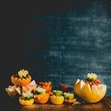 Variety of colorful citrus fruits half on table at dark background. Copy space. Tropical citrus fruits assortment. Vitamin C. Healthy lifestyle