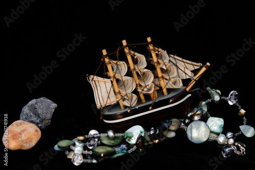 A model of a sailing ship stands on a necklace resembling a sea wave. Concept - hunt for underwater treasure © yuryastankov