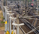 Row of electric lanterns next to pantographs on a platform next to the rails of the railway