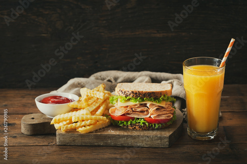 sandwich with ham, french fries and glass of orange juice © Nitr