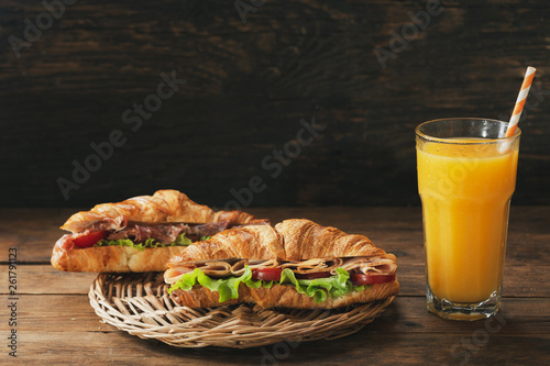 croissant sandwiches with ham and glass of orange juice © Nitr