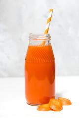 fresh carrot juice in a bottle, closeup