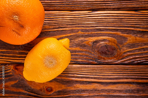 canvas print picture rotten, spoiled lemons and oranges on wooden background flat lay