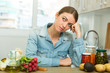 Tired woman sitting at home kitchen