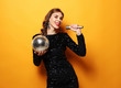 woman in evening dress holding microphone and disco ball