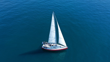 Aerial drone birds eye view of sail boat cruising in the deep blue Aegean sea, Greece