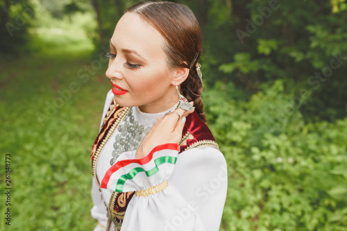 A woman in traditional embroidered Turkic Eastern clothes performs a national dance in the Park