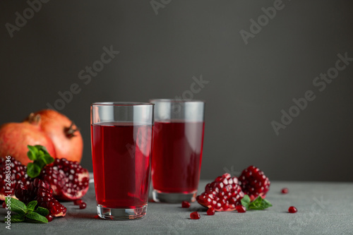 Leinwandbild Motiv Pomegranate juice in a two glasses on gray background.