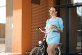 Young attractive woman riding through the park after work. Beautiful lady cycling during sunset. Bike as a trendy transport. Healthy outdoors activity on a warm summer day. Bicycle trend in the city.