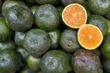 Ripe sliced citrus lying on pile of green oranges