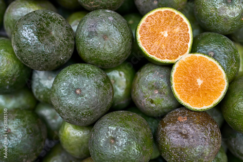 canvas print picture Ripe sliced citrus lying on pile of green oranges