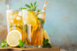Leinwanddruck Bild - Traditional iced tea with lemon and ice in tall glasses on a wooden rustic table. With copy space
