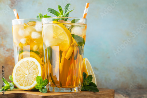 Traditional iced tea with lemon and ice in tall glasses on a wooden rustic table. With copy space - 261893129