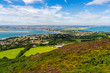 Dublin city view from the top of Howth Head, Ireland. Irish landscape with hills covered in lovely wildflowers, heather and gorse and houses built at the seashore, on a bright summer day. - 261941391
