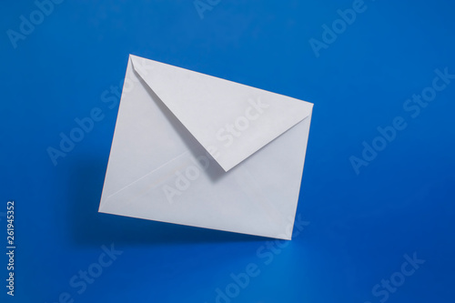 Blank white paper envelope on a single-colored background - 261945352