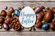 Chocolate easter eggs and bunnies on a rustic wooden background - 261950158