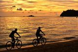 Two cyclist relaxing and enjoyed beautiful sunset along the beach in pangkor island, perak malaysia