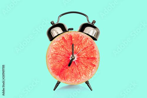 Grapefruit slice on alarm clock, blue pastel background. fruit and vitamins diet at breakfast nutrition concept © Delphotostock