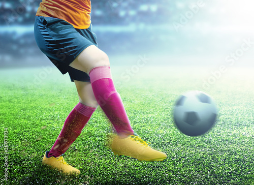 canvas print picture Football player woman in orange jersey kicking the ball