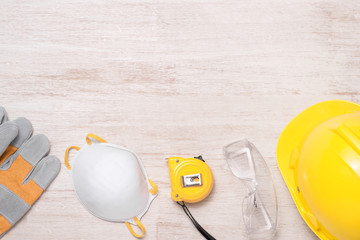 Construction site safety. Protective hard hat, gloves, glasses and masks on wooden background, copy space, top view