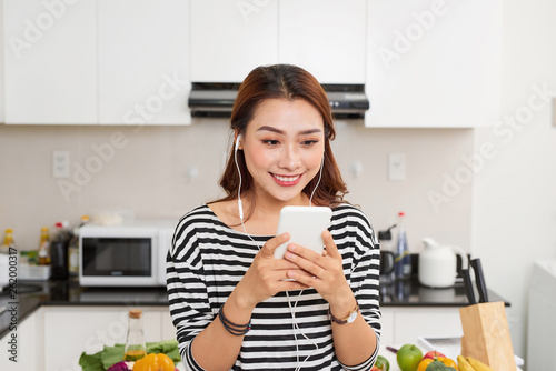 Portrait of a cute young woman in headphones wearing apron using mobile phone at the kitchen - 262000317