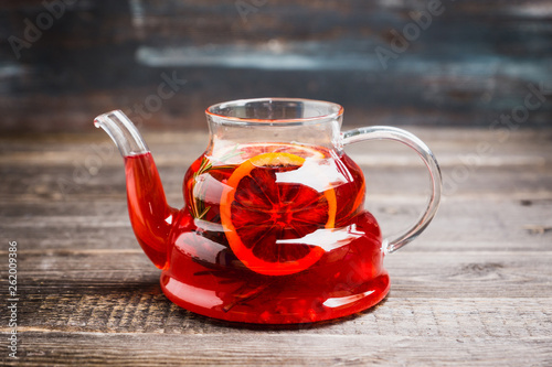 Fruit drink based on raspberry with red orange slice in glass teapot. Selective focus. Shallow depth of field. © maxandrew