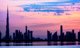 Stunning view of the silhouette of the Dubai skyline during sunset with the magnificent Burj Khalifa and many other buildings and skyscrapers reflected on a silky smooth water. Dubai.