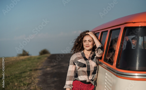A young girl on a roadtrip through countryside, leaning on a minivan. © Halfpoint