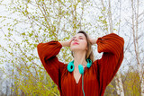 Style adult woman with headphones and burgundy color blouse on birch trees background