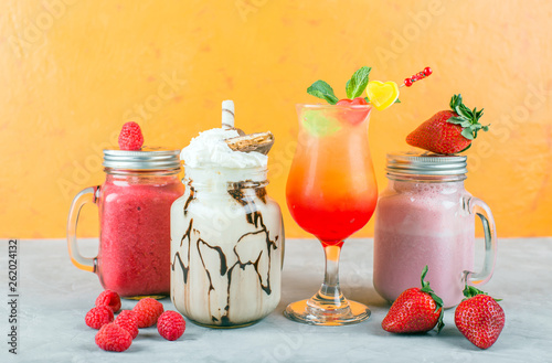 Various non-alcoholic cocktails, raspberry and strawberry smoothies, bright orange background © yakovlevadaria