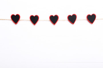 Small black hearts hanging on white background