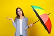 Leinwandbild Motiv Young girl with colorful umbrella on yellow background