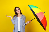 Young girl with colorful umbrella on yellow background