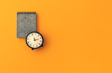 space note and alarm clock on vintage pastel background