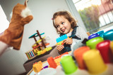 Cute child playing on table indoor, selective focus.