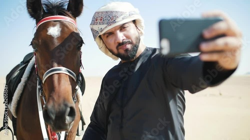 Man with his horse in Dubai, walking and riding in the desert