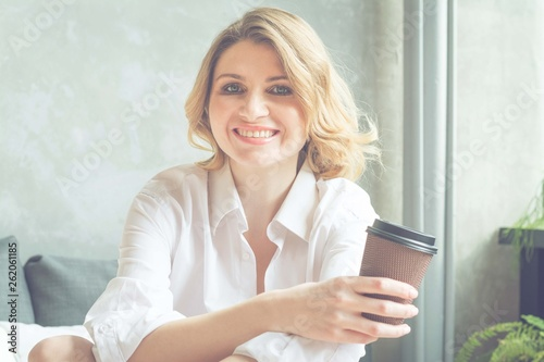 canvas print picture Beautiful blonde woman in a white shirt looks into the camera, drinks coffee and smiles, morning mood