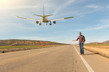 Man hitchhiking and airplane landing on the road