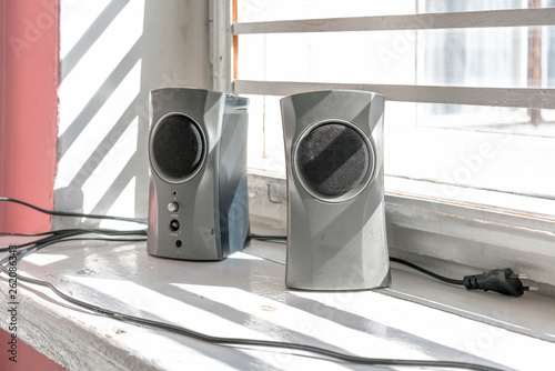 two gray musical speakers on an old wooden windowsill - 262086343