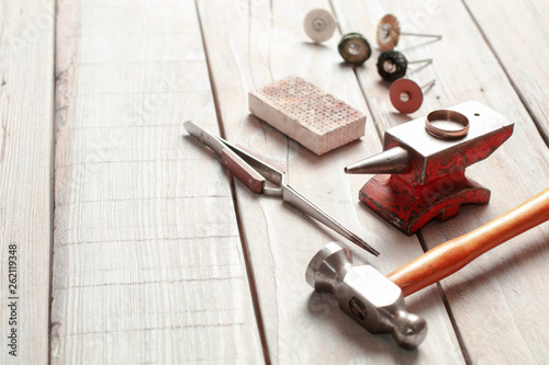 Top view of different goldsmiths tools on the jewelry workplace. Desktop for craft jewelry making with professional tools. Top view of tools over rustic wooden background. © Bugaev