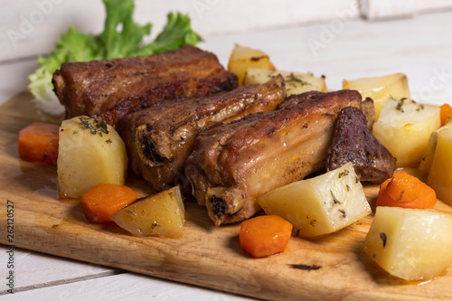 Roasted pork ribs with thyme potatoes over white wooden background, Eastern cuisine - 262120527