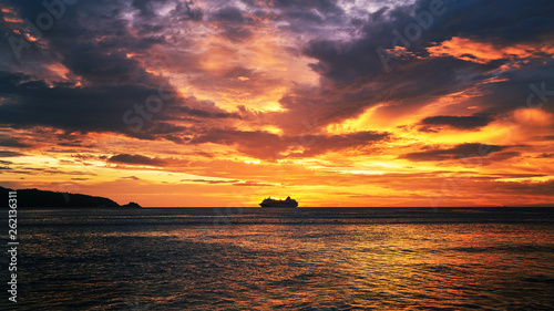 dramatic sunset skyline with seascape and travel cruise ship