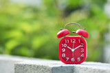 Red clock showing at 10.10 with blurred background.