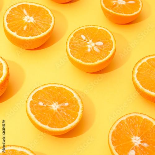 canvas print picture Orange juicy oranges split in half on yellow
