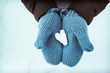 Heart shaped snow in blue knit mittens in the wintertime on a snowy day, blue tone