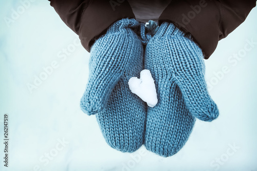 canvas print picture Heart shaped snow in blue knit mittens in the wintertime on a snowy day, blue tone