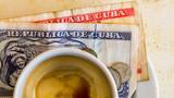 Havana Cuba. Close up of Cuban pesos and espresso coffee on wood table surface.