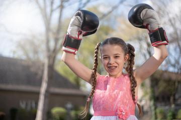 Mädchen mit der Zahnspange trägt Boxhandschuhe