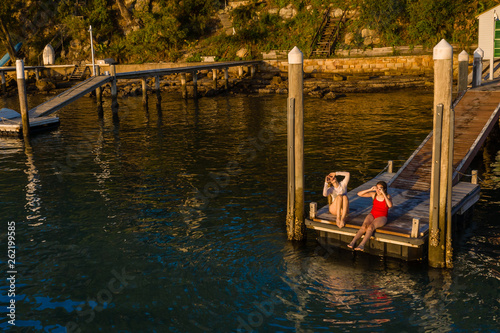 two young woman sitting on a jetty in the afternoon light © gillianvann