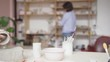 Tracking left close-up of young female ceramic artist making clay bowl in art studio, her colleague examining artworks in background